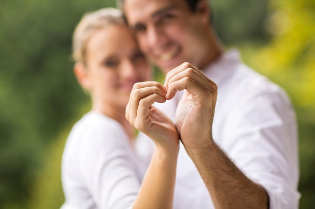 young couple making heart with hands